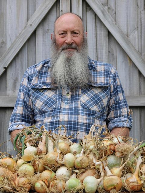 A person in a blue plaid shirt next to a bunch of raw onions